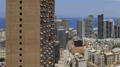 Artist Jad El Khoury installs colourful window shades to war-torn skyscraperin Beirut